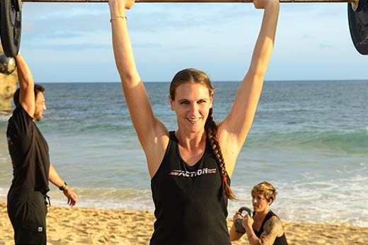 A pretty, fit girl lifts weights on the beach in Kauai for Physical Therapy
